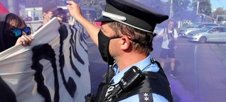 Polizist droht Demonstranten mit Waffe